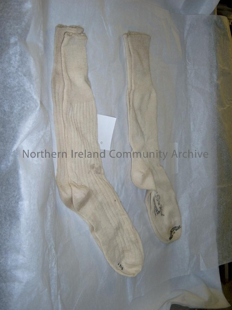 ww2 2 pairs of cream woollen socks. One pair marked All pure wool, made in Australia. Fit wear 11 ½. Other pair are ribbed in design and marked 11 ½ on sole of foot. Both pairs are stapled together. (1645)