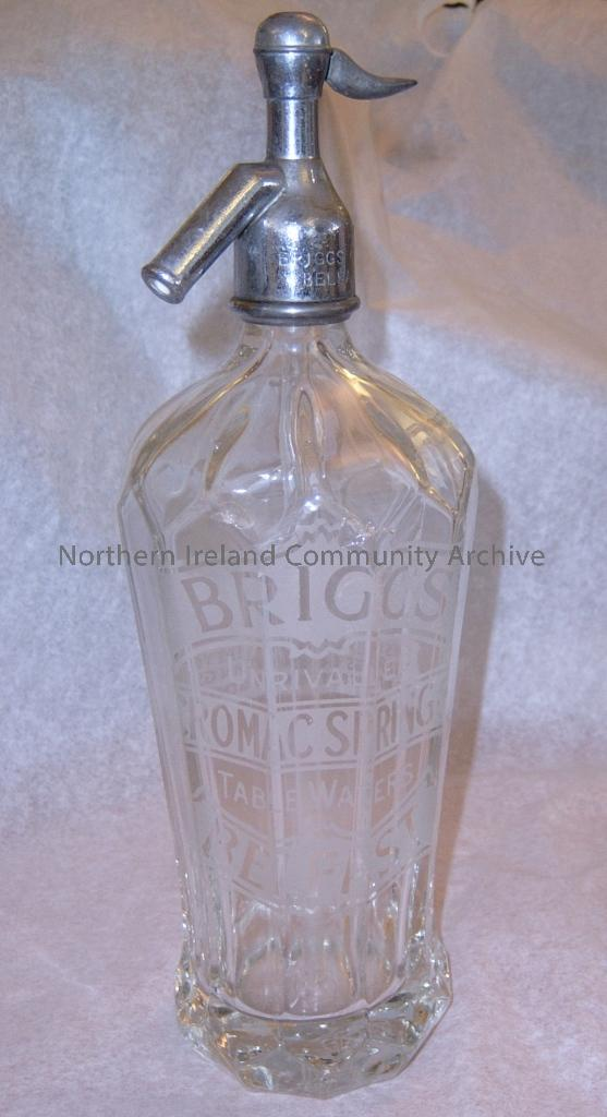 Glass bottel and metal soda syphon. Frosted on the front of the bottle, Briggs unrivalled Cromac Springs. Table waters, Belfast. Mayo Syphons Ltd, London. Inscribed onto the metal syphon at the top is Briggs Cromac Springs Belfast /40. Metal syphon also s (2356)