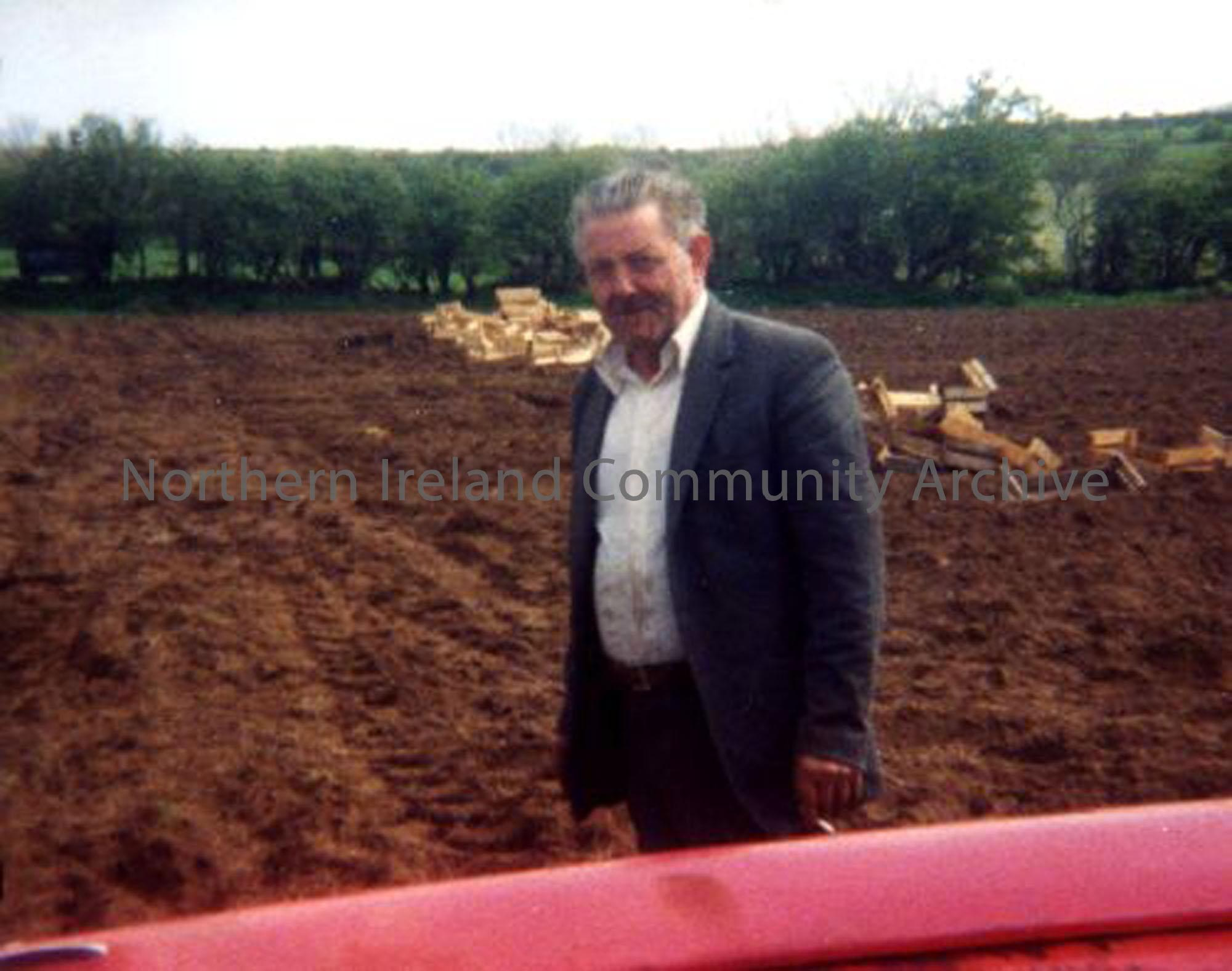 Norman Walker seen here sowing potatoes. Potato boxes can be seen behind him in the field. Norman lives now in Mosside and was originally from Bushside. (2555)