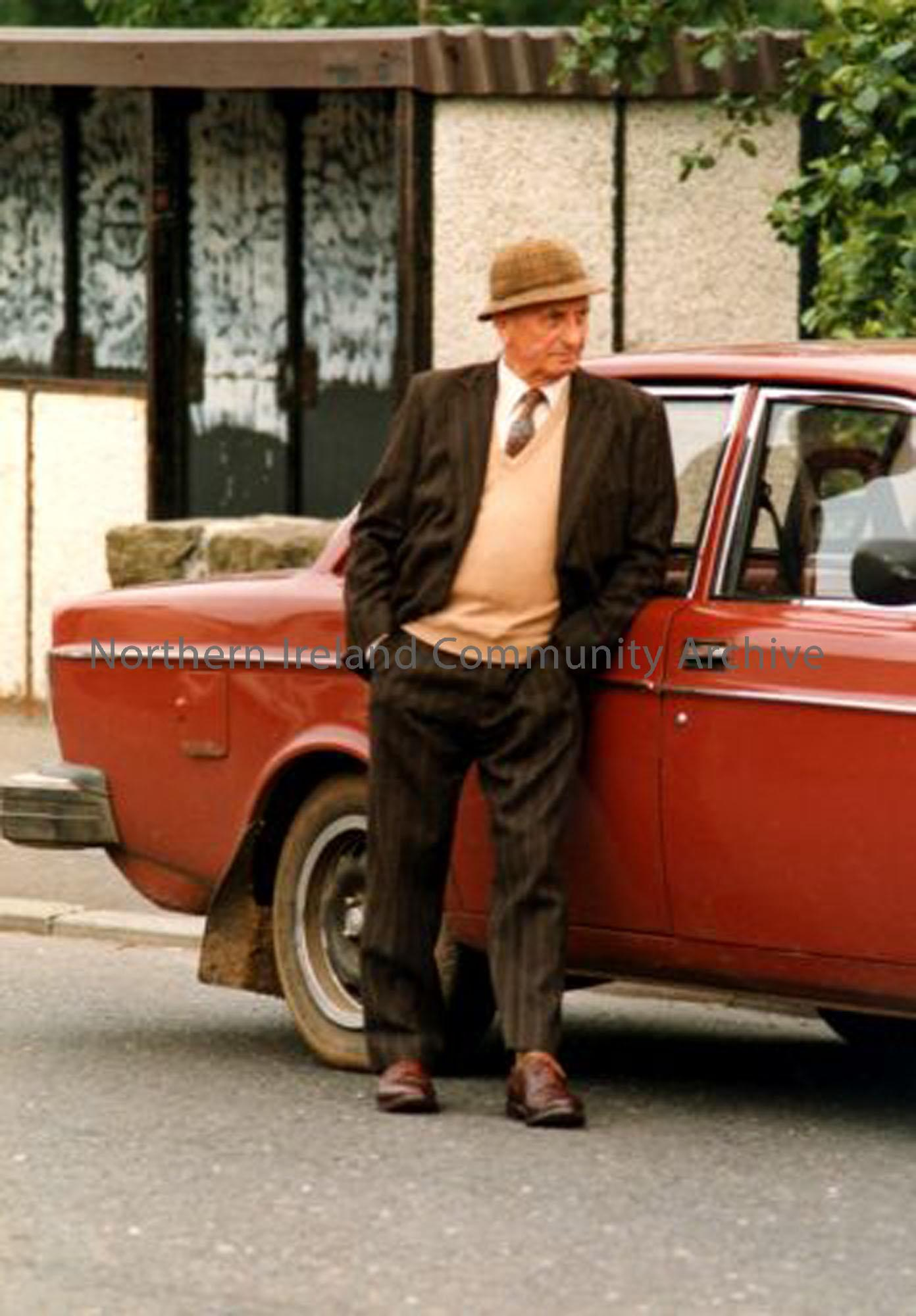 Jack Campbell, deceased, standing beside his car alongside the first bus shelter in Dervock. He was famous for a breed of pigs called Carncullagh Whites. His family sold the farm and now farm in Scotland. (3660)